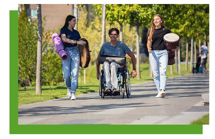 Aparecen 3 personas paseando una de ellas en silla de ruedas